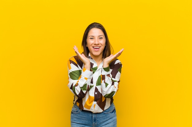Latin american woman feeling shocked and excited, laughing, amazed and happy because of an unexpected surprise isolated against yellow wall Premium Photo