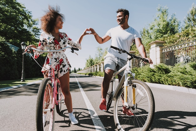 Latin couple go cycling and showing finger heart Premium Photo