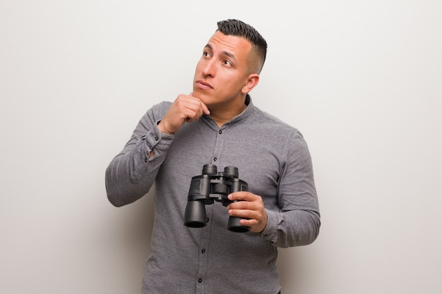 Latin man relaxed thinking about something looking at a copy space. he is holding a binoculars. Premium Photo