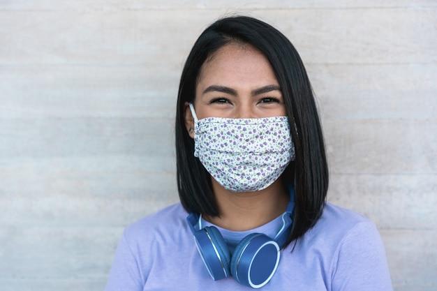 Поздняя миллениальная девушка улыбается в защитной маске Premium Фотографии