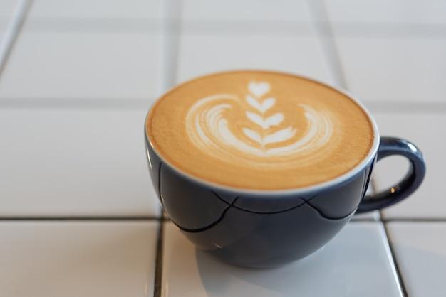 Latte art coffee cup on white table Premium Photo