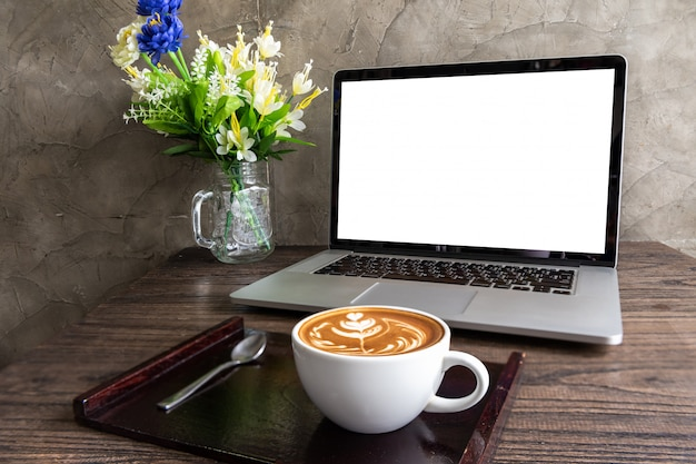 Latte art coffee with blank screen of laptop computer on wooden table Premium Photo