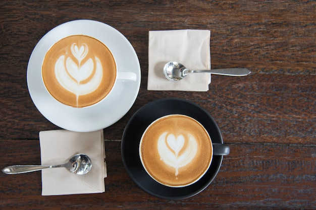 Latte art heart shape coffee cup on wooden table background before breakfast Premium Photo