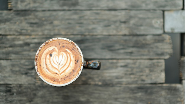 Текстура сердца latte кофе на деревянном поле. Premium Фотографии