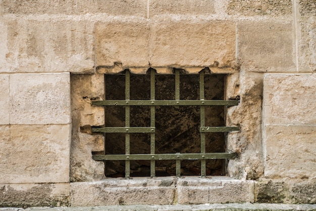 Lattice with a hole in the window in the old town Premium Photo