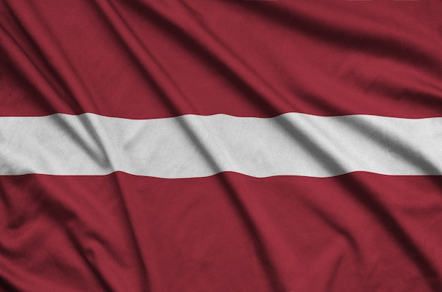 Latvia flag is depicted on a sports cloth fabric with many folds. Premium Photo