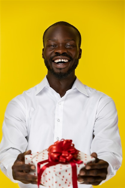 Laughing bearded young afroamerican guy is holding one present in two hands in white shirt Free Photo