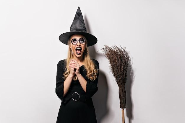 Смеющаяся блондинка наслаждается маскарадом в хэллоуин. добродушная ведьма позирует в черной шляпе. Бесплатные Фотографии