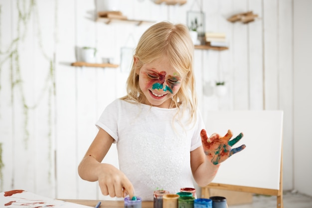 Laughing blonde girl in white t-shirt with paint on her face and hands captured by creative impulse. child enjoying art. Free Photo