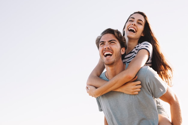 Laughing boyfriend carrying laughing girlfriend at the beach Premium Photo