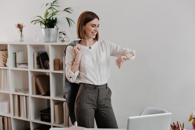 Ridendo donna d'affari in camicetta bianca e pantaloni grigi sta guardando l'orologio da polso, in piedi contro i mobili per ufficio. Foto Gratuite