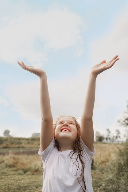 Laughing child spread its arms and catches raindrops and sunrayses. Premium Photo