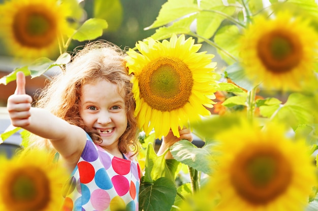Laughing child with sunflower, showing thumbs up. Premium Photo