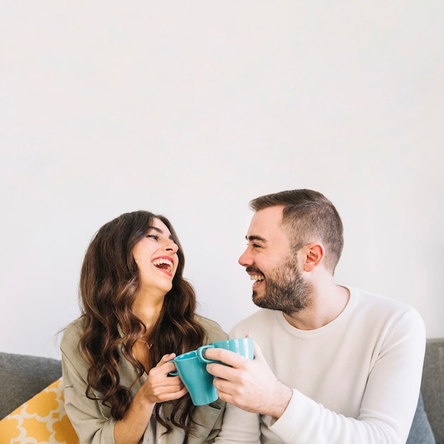 Laughing couple with cups Free Photo