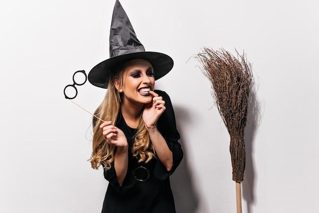 Смеющаяся кудрявая ведьма, наслаждаясь хеллоуином. крытый портрет добродушного волшебника изолированного на белой стене. Бесплатные Фотографии