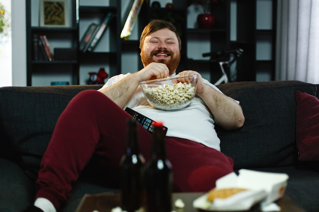 Laughing fat man sits on the sofa, eats pop-corn and watches tv Free Photo