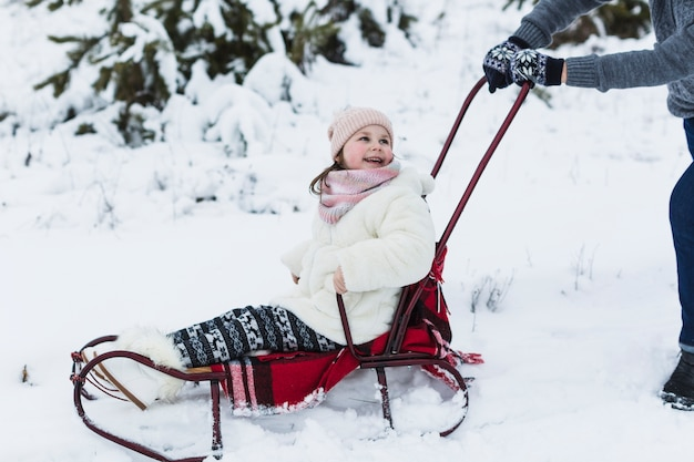 Laughing girl riding sleigh with father Free Photo