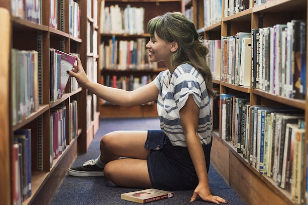 Laughing girl taking book from library Free Photo