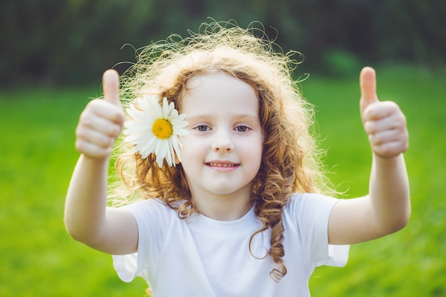 Laughing girl with daisy in her hairs, showing thumbs up. Premium Photo