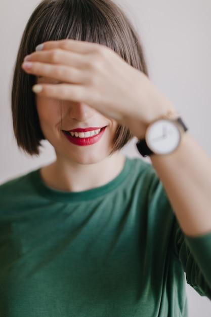 La ragazza di risata con le labbra rosse copre i suoi occhi. foto interna del modello femminile piacevole in posa di orologio da polso alla moda. Foto Gratuite