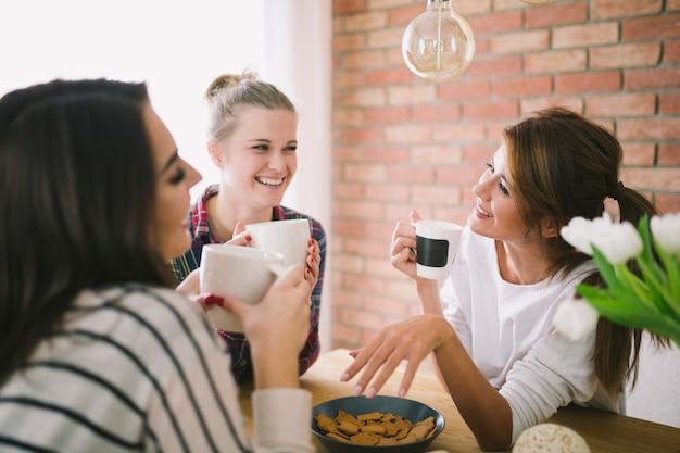 Laughing girls drinking tea and talking Free Photo