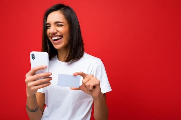 電話とクレジットカードを保持している背景に分離された日常服を着て幸せな若い女性を笑う Premium写真