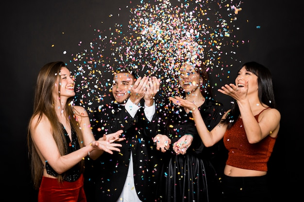 Laughing ladies and guy in evening cloths tossing confetti Free Photo