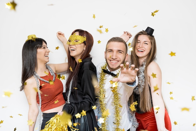 Laughing ladies and guy in evening wear between ornament confetti Free Photo