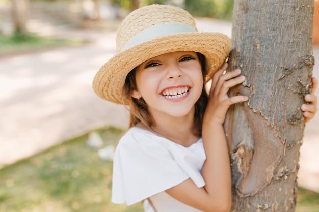 Bambina che ride con la pelle leggermente abbronzata in posa nel parco toccando l'albero. ritratto di close-up all'aperto di allegro ragazzo dai capelli scuri in cappello vintage con nastro divertendosi in giardino. Foto Gratuite