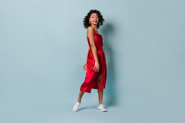 Смеющаяся красная женщина в белых кедах, глядя на фронт Бесплатные Фотографии