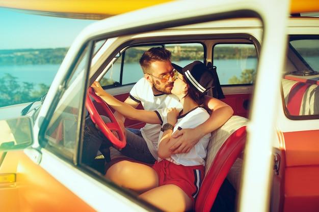 夏の日の遠征中に車に座って笑うロマンチックなカップル 無料写真