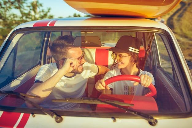 Смеющаяся романтическая пара, сидя в машине во время поездки. пара, пикник в летний день Бесплатные Фотографии