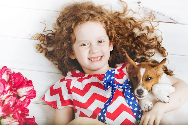 Laughing toothless girl hugging a puppy. Premium Photo
