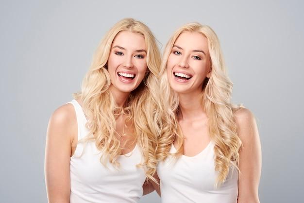 회색 배경에 웃는 쌍둥이 무료 사진