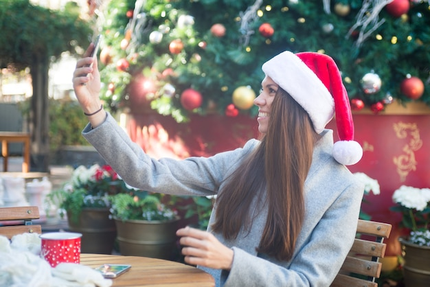Laughing woman in santa hat taking selfie near cristmas tree in cafe outside Premium Photo