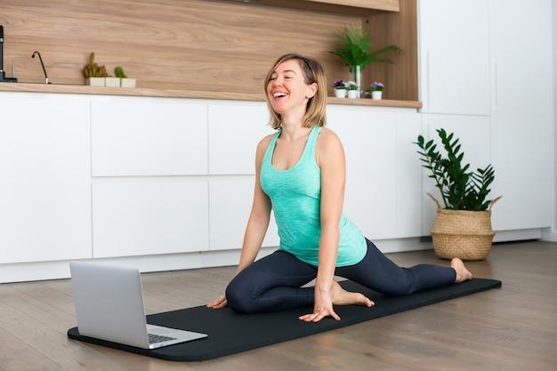 집에서 온라인으로 요가를하는 동안 노트북 앞에서 스트레칭 웃는 여자 프리미엄 사진