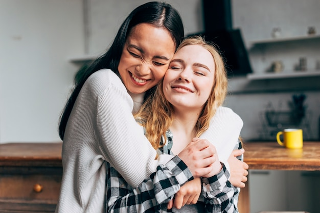 Laughing women embracing at home Free Photo
