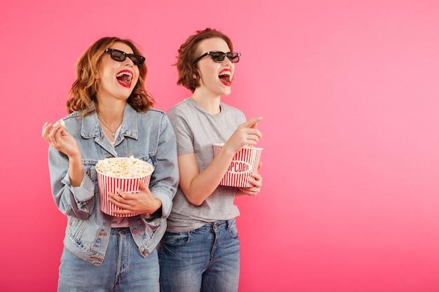 Laughing women friends eating popcorn watch film. Free Photo