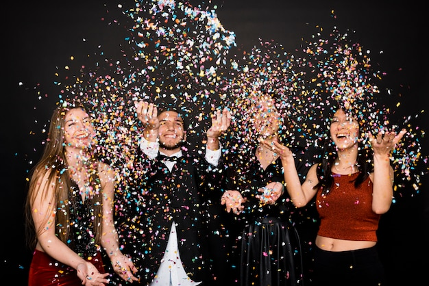 Laughing women and man in evening cloths tossing confetti Free Photo