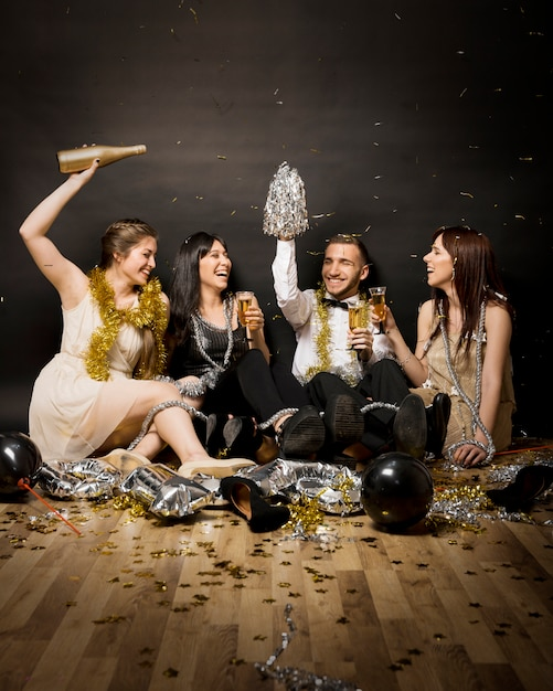 Laughing women and man in evening wear with glasses of drinks on floor Free Photo