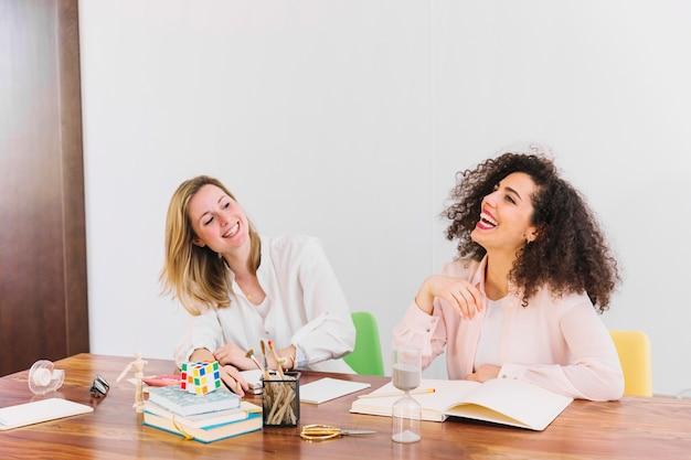Смеющиеся женщины, обучающиеся за столом Бесплатные Фотографии