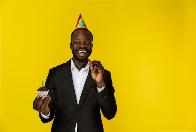 Laughing young afroamerican guy in black suit and birthday hat with burning candle Free Photo