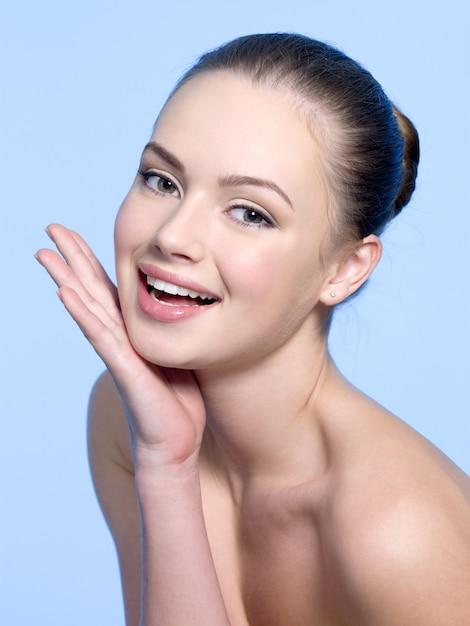 青の顔に手で若い美しい少女を笑う 無料写真