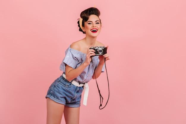 사진을 찍는 데님 반바지에 젊은 여자를 웃 고있다. 분홍색 배경에 고립 된 카메라와 핀 업 소녀의 스튜디오 샷. 무료 사진