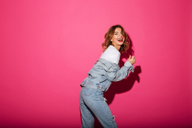 Laughing young woman isolated over pink Free Photo