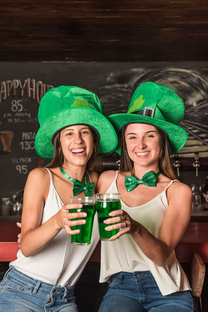 Laughing young women in saint patricks hats hugging and holding glasses of drink at bar counter Free Photo