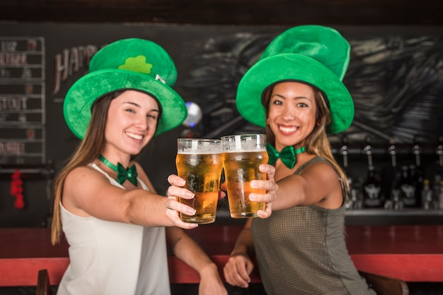 Laughing young women in saint patricks hats showing glasses of drink at bar counter Free Photo