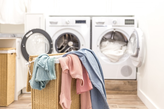 Laundry basket with dirty clothes with washing and drying machines on the background Premium Photo
