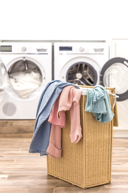 Laundry room with basket and washing and drying machines on background Premium Photo
