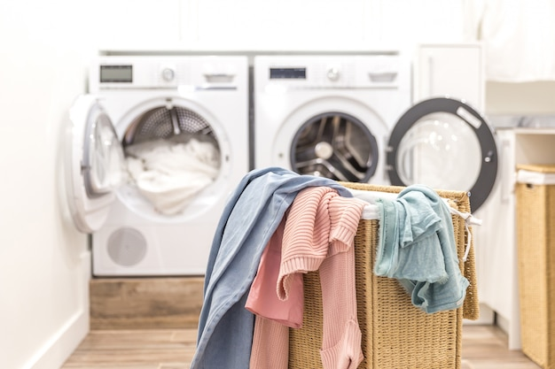 Laundry room with basket and washing and drying machines Premium Photo